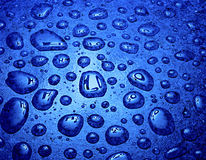 Water droplets with reflection h2o symbol. Water droplets on blue background with reflection of h2o symbol Royalty Free Stock Image