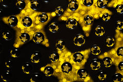 Water droplets with reflections of golden stars Royalty Free Stock Photo