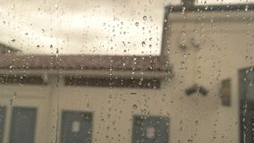 Water droplets on train window. Blurred sky and building. Bid farewell to home town stock video