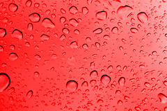 Water Drops. On Red Glass Royalty Free Stock Photos