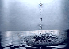 Water drops. Falling into the foam Royalty Free Stock Photo