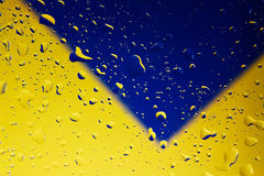 Water drops. On clear glass with yellow/blue background Stock Image