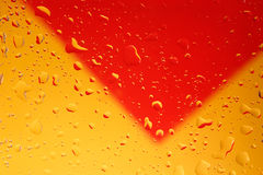 Water drops. On clear glass with yellow/red background Stock Photos