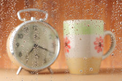 Water drops with alarm clock and coffee cup. Focus of water drops (alarm clock and coffee cup for background Stock Images