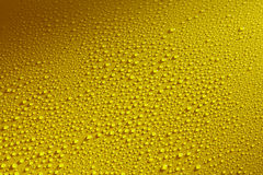 Water drops beading on a yellow metal surface Royalty Free Stock Image
