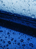 Water drops on blue. Water drops gathered on blue metal stock photography