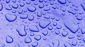 Water drops on blue. Details of large water drops and moisture on a smooth, blueish surface Stock Photos
