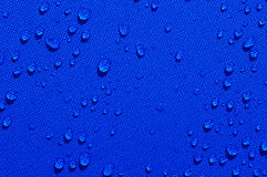 Water drops on blue fabric Stock Photography