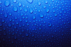 Water drops on blue glass in dark Royalty Free Stock Photo