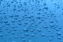Water drops in blue surface Royalty Free Stock Images