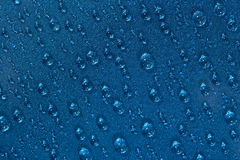 Water drops on the blue surface Stock Image