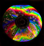 Water drops on the CD. Closeup of water drops on a multicolored surface of CD Stock Image