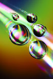 Water drops on CD with colorful rainbow Stock Images