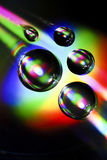 Water drops on CD with colorful rainbow Stock Photo