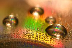 Water Drops on CD and DVD. abstract wallpaper. Water Drops on CD and DVD. Colorful background Stock Images