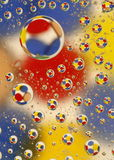 Water Drops with circles. Water drops of various sizes on glass with a background with red, yellow and blue circles Royalty Free Stock Photo