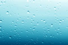 Water drops on clean glass blue background Royalty Free Stock Image