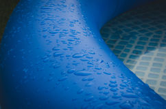Water drops on an edge of the blue inflatable pool. Water drops on an edge of the inflatable pool Stock Photos
