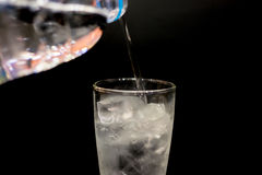 Water drops fall down in the glass at black background. Water drops fall down in the glass at black background Royalty Free Stock Images