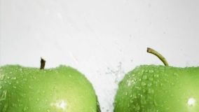 Water drops falling in super slow motion on apples Royalty Free Stock Image
