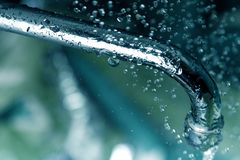 Water drops and faucet Stock Images