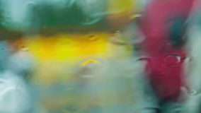 Water Drops Flowing Down On Glass During Rain. This is a shot from inside of the car or a house of water drops gently falling on glass and flowing down during stock video footage