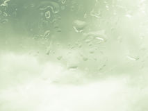 Water drops on glass with cloud background Stock Images