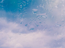 Water drops on glass with cloud background Royalty Free Stock Photo