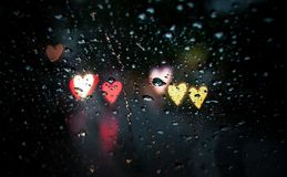 Water drops on glass with heart shaped light in background. Night photograph of water droplets on glass with heart shaped bokeh in background Stock Images