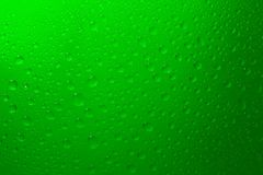 Water Drops on Green. Water drops sprinkled on a green glowing background royalty free stock photography