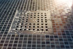Water drops on metal gutter in the evening sunsh Stock Image