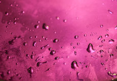 Water Drops on Metal. Water drops lit by pink light on a metal surface Stock Photography