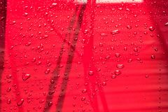 Water drops on metal surface. Abstract background, drops of wate. R red car Royalty Free Stock Image
