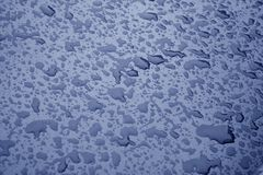 Water drops on metal surface in blue color. Abstract background and texture Stock Photos