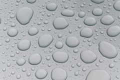 Water drops on metal surface. Water drops on metalized car paint, hence the tiny grain-looking dots on the surface Royalty Free Stock Photos