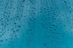 Water drops on metal surface. Water drops on metalized car paint, hence the tiny grain-looking dots on the surface Royalty Free Stock Images