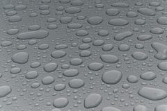 Water drops on metal surface. Water drops on metalized car paint, hence the tiny grain-looking dots on the surface Stock Photography