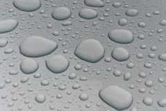 Water drops on metal surface. Water drops on metalized car paint, hence the tiny grain-looking dots on the surface Stock Image