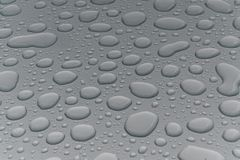 Water drops on metal surface. Water drops on metalized car paint, hence the tiny grain-looking dots on the surface Stock Photo