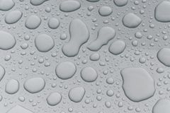 Water drops on metal surface. Water drops on metalized car paint, hence the tiny grain-looking dots on the surface Stock Images