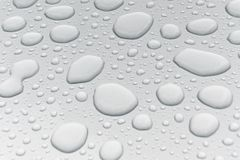 Water drops on metal surface. Water drops on metalized car paint, hence the tiny grain-looking dots on the surface Stock Photos