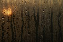 Water drops on the misted glass. View of a sunset through water drops on the misted glass Stock Images
