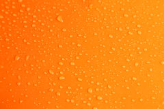 Water drops on orange background, close up Royalty Free Stock Image