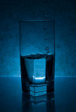 Water Drops Pouring into Glass Royalty Free Stock Image