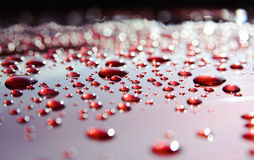 Water drops on red with beautifull bokeh. Clear, transparent water droplets are scattered on the red surface. There is a beautifull bokeh on a background Royalty Free Stock Photos