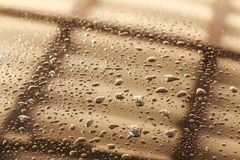 Water drops in a shiny metallic surface with table re Royalty Free Stock Image