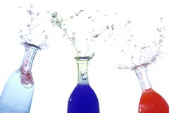 Water drops shooting out of bottles Royalty Free Stock Photography