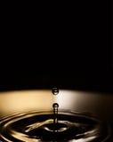 Water drops. splash. Bronze and dark liquid waves. Black background. Stock Photo