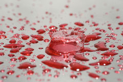 Water drops and splash. Red water drops and splash on silver background Stock Photos