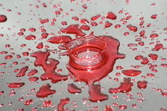 Water drops and splash. Red water drops and splash on silver background Royalty Free Stock Photos
